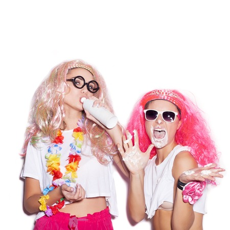 happy couple white background: Funny girls in colored wigs and glasses stained with cream on white background not isolated Stock Photo
