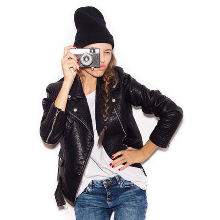Pretty girl making photo using noname retro camera. White background, not isolated Stock Photo