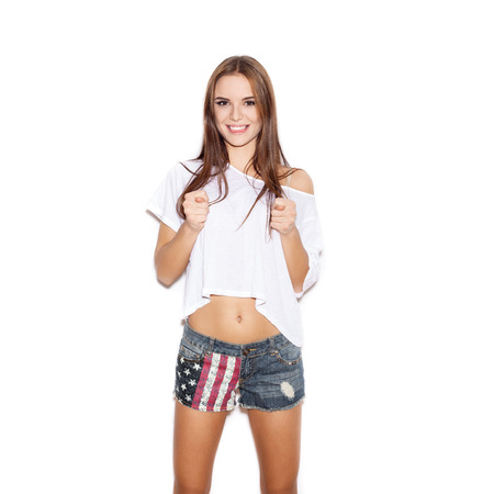 Young woman showing rude gesture with both hands over white background, not isolated photo