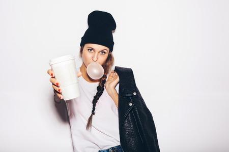 swag meisje in zwarte muts geven kop koffie en het opblazen zeepbel van kauwgom. Moderne mode meisje. Witte achtergrond, niet geïsoleerd, niet geïsoleerd