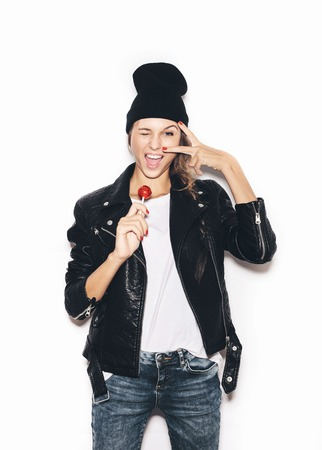 Funky hipster girl  saluting, winking and  sucking lollipop. White background, not isolated