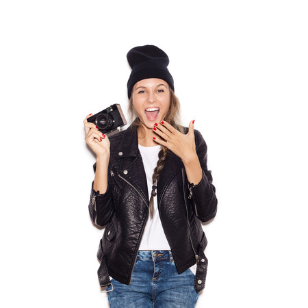 photo shooting: Happy hipster girl in black beanie having fun with vintage noname camera. Laughing young woman. White background, not isolated