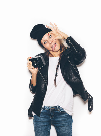 Hipster girl in hat having fun with vintage noname camera. White background, not isolated photo