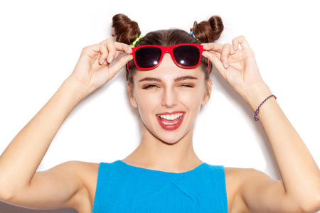 trendy: Happy Brunette Woman in sunglasses. Beauty girl with bright makeup hairstyle with horns in a blue dress having fun. On a white background, not isolated Stock Photo