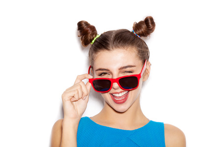Surprised Brunette Woman in sunglasses. Beauty girl with bright makeup hairstyle with horns in a blue dress having fun. On a white background, not isolated Standard-Bild