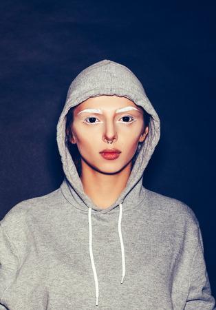 black eyes: Donna con gli occhi neri e sopracciglia bianche. Hipster ragazza in felpa con cappuccio grigio su sfondo scuro, non isolato. Archivio Fotografico