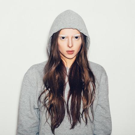 black eyes: Donna con gli occhi neri e sopracciglia bianche. Hipster ragazza in grigio hoodie, non isolato Archivio Fotografico