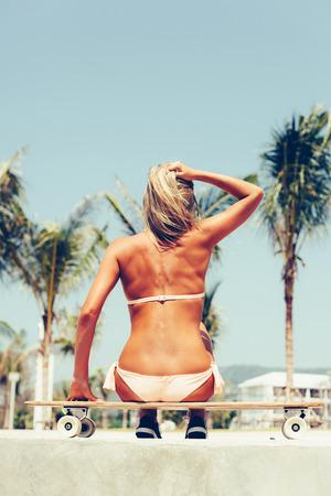 blonde bikini: Beautiful sporty woman sitting on longboard in sunny day. Skateboard Outdoor lifestyle
