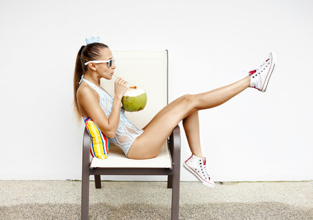 trend: fashion young woman  drinking coconut water and sitting on chair . Outdoor lifestyle portrait