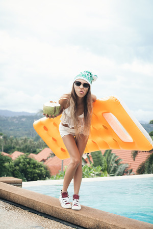 Beautiful young woman with coconut   Relaxing in a pool. Outdoor lifestyle portrait of a sporty girl photo