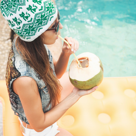 Beautiful young woman in bikini drinking coconut juice. Female legs in the pool water. Outdoor lifestyle portrait Standard-Bild