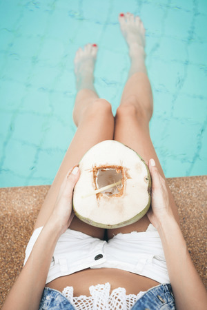 coconut drink: portrait of cute girl with coconut cocktail in the tropical pool. Vertical. Outdoors lifestyle Stock Photo