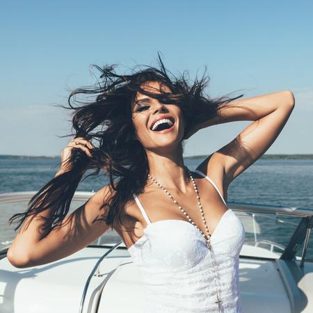 행복 한 젊은 여자는 여름에 열린 바다에서 호화 보트에 재미가있다. 백인 여성 모델
