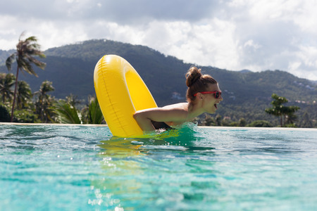 inner tube: Young pretty fashion woman body posing in summer in pool with clear water lying inner tube and having fun Stock Photo