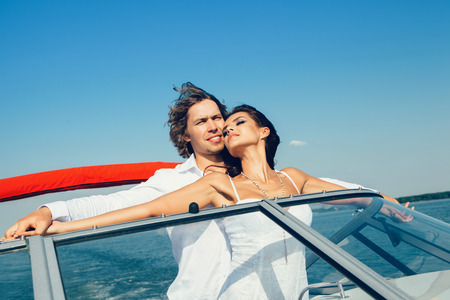 sexy kiss: Young couple loving each other. Beautiful man and woman on a sea voyage on a yacht.
