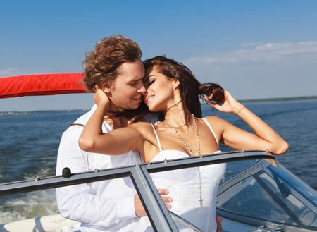 pareja abrazada: Joven pareja bes�ndose. Hombre y mujer en un viaje por mar en un yate.