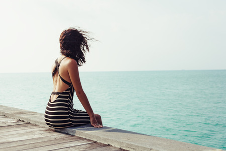 Young pretty woman sitting alone on the pier near the sea and looking on the water and waiting for somebody in ocean