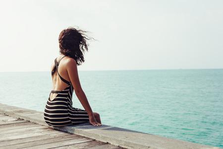 Piuttosto giovane donna seduta da sola sul molo vicino al mare e guardando in acqua e in attesa di qualcuno in oceano