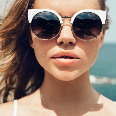 Closeup fashion summer portrait of pretty young sensual woman in sunglasses posing on the beach on vacation Standard-Bild