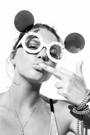 femme sexe: Jeune fille blonde dans des lunettes de soleil embrasser doigt du milieu. Mode de vie ext�rieur close-up d'une femme sexy. Virage en noir et blanc