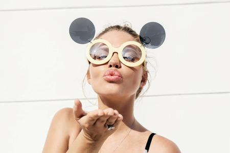 bacio: Carino bionda che indossa occhiali da sole e l'invio di un bacio. Stile di vita Ambientazione esterna