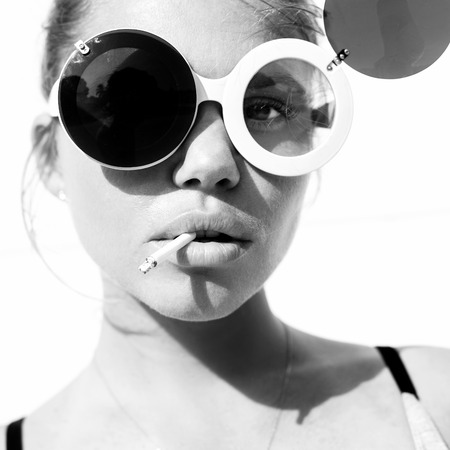 Close-up of beauty girl in trendy sunglasses  with cigarette. Toned black and white. White background, not isolated