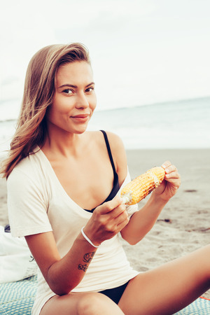snacking: Outdoor summer style fashion portrait of young beautiful sensual woman posing on the beach on vacation. Girl holding corn and smiling. Snacking on the sea.