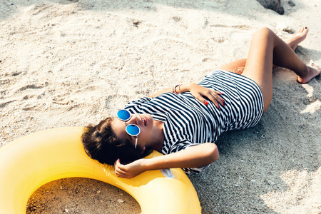 hot weather: Beautiful woman in sunglasses lying on a beach in sand at summer day. Outdoor lifestyle portrait of girl Stock Photo