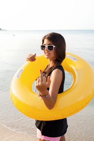 ass fun: Girl showing rude gesture. Happy young woman having fun time on beach.  Outdoors lifestyle portrait