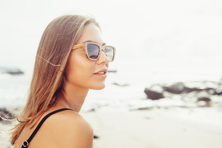 Outdoor fashion portrait summer beach style of young beautiful woman fresh face smiling on the beach of tropic island having fun on vacation in bikini and sunglasses