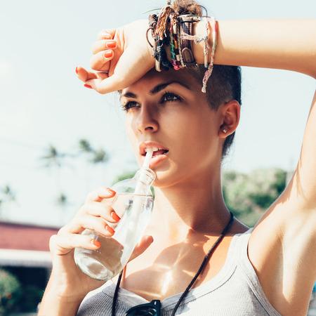 tomando agua: Retrato de mujer agua potable joven. Chica con estilo contra la escena urbana