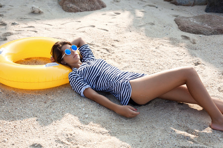 hot girl lying: Beautiful woman in sunglasses lying on a beach in sand at summer day. Outdoor lifestyle portrait of girl Stock Photo