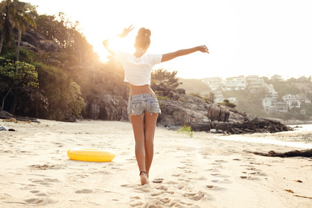 carefree woman dancing in the sunset on the beach. Outdoors lifestyle portrait of girl
