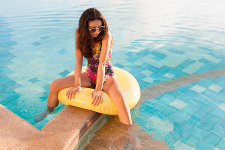 tanned body: Young pretty woman with perfect tanned body lying on yellow air mattress in the pool in summer and having fun. Outdoor fashion portrait of happy girl in sunglasses