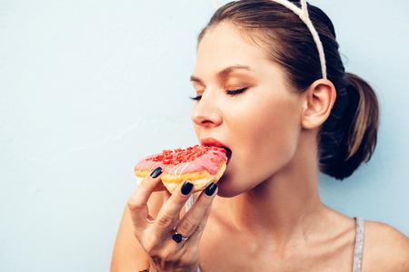 맛있는 도넛을 먹고 매력적인 갈색 머리 섹시 한 여자. 예쁜 여자의 야외 라이프 스타일 초상화 스톡 콘텐츠