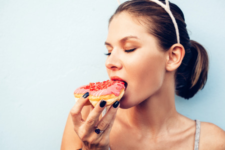 Attractive brunette sexy woman eating tasty donut. Outdoors lifestyle portrait of pretty girl