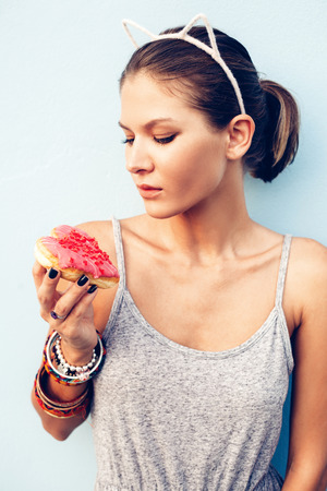 pretty brunette woman: Brunette sexy woman holding tasty donut. Outdoors lifestyle portrait of pretty girl