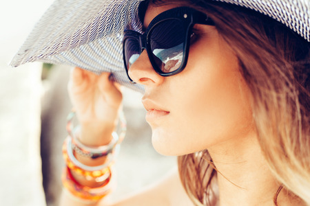 Detailní záběr na tvář mladé letní sexy žena na sobě klobouk a sluneční brýle. Venku životní styl portrét