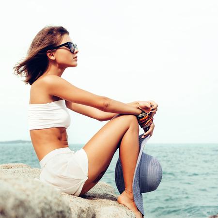sensual: Retrato de la moda Soleado de la mujer sensual joven bonita que presenta en las rocas por sí sola en la costa del océano. Aire libre retrato estilo de vida