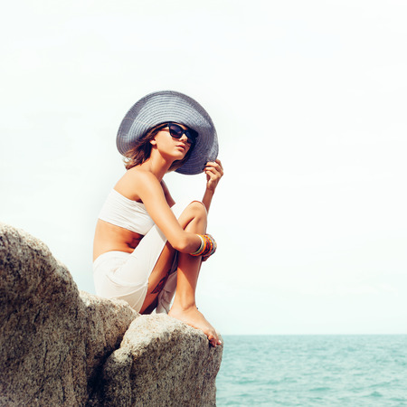 woman alone: Outdoor summer sunny fashion portrait of pretty young sensual woman posing in hat and white dress on the rocks and have fun alone on the ocean seashore. Outdoors lifestyle portrait