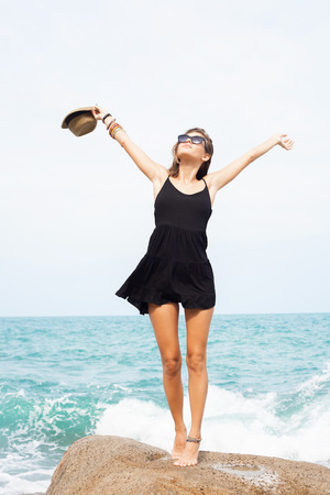 black dress: Outdoor summer sunny fashion portrait of pretty young sensual woman posing in black dress on the rocks and have fun alone on the ocean seashore. Outdoors lifestyle portrait Stock Photo