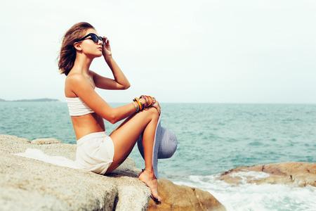 Bastante joven mujer sensual que presenta en las rocas solo en la orilla del mar océano. retrato estilo de vida al aire libre Foto de archivo - 39857703