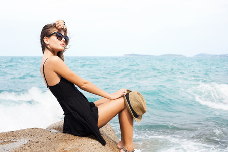 sexual background: Outdoor summer sunny fashion portrait of pretty young sensual woman posing in black dress on the rocks on the ocean seashore. Outdoors lifestyle portrait