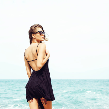 Outdoor summer sunny fashion portrait of pretty young sensual girl posing in sunglasses and black dress on the rocks on the ocean seashore. Outdoors lifestyle portrait Stock Photo