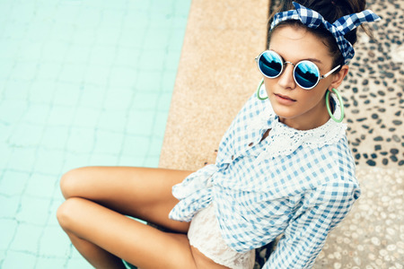 happy rich woman: Fashion photo of sexy beautiful Girl in plaid shirt and sunglasses relaxing beside a swimming pool. Outdoors lifestyle  portrait Stock Photo