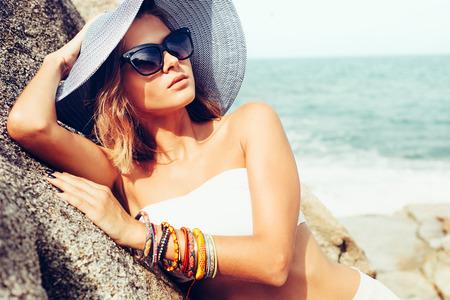 gafas de sol: Mujer del verano la moda de moda posando en las rocas por sí sola en la costa del océano. Aire libre retrato estilo de vida