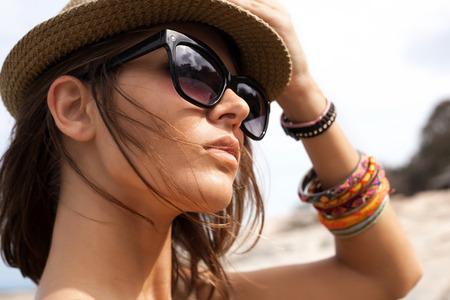 Close-up van jonge zomer sexy vrouw draagt een hoed en zonnebril. Buitenleven levensstijl portret