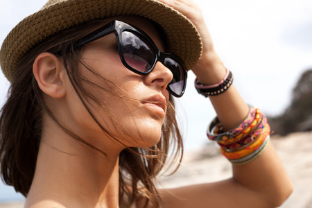 Closeup of young summer sexy woman  wearing a hat  and sunglasses. Outdoors lifestyle portrait
