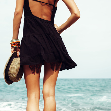 Outdoor summer sunny fashion portrait of pretty young sensual blonde woman posing in black dress on the rocks on the ocean seashore. Outdoors lifestyle portrait