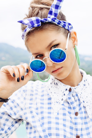 Fashion photo of sexy beautiful woman in plaid shirt and sunglasses. Outdoors lifestyle portrait